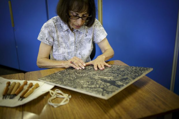 KILE BREWER/STAFF - Mollie Doctrow works on a woodcut in one of the studios at South Florida State College. Doctrow will retire in June after working as the SFSC Museum of Florida Art and Culture curator for more than a decade.